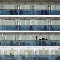 A passenger stands on the balcony of the cruise ship Diamond Princess anchored at the Yokohama Port in Yokohama, near Tokyo, Feb. 7, 2020 (AP Photo/Eugene Hoshiko)