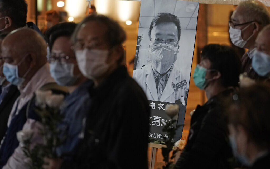 People wearing masks, attend a vigil for Chinese doctor Li Wenliang, in Hong Kong, February 7, 2020. (AP Photo/Kin Cheung)