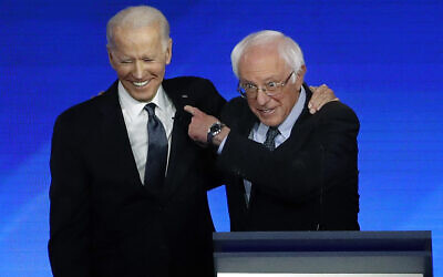Former vice president Joe Biden, left, embraces Sen. Bernie Sanders during a Democratic presidential primary debate, February 7, 2020, hosted by ABC News, Apple News, and WMUR-TV at Saint Anselm College in Manchester, New Hampshire (AP Photo/Elise Amendola)