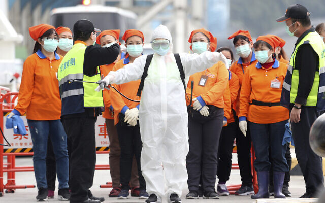 An epidemic prevention worker in a protective suit stands by to get on board the cruise ship SuperStar Aquarius docked at Keelung port in New Taipei City, Taiwan, Saturday, Feb, 8, 2020. (AP/Chiang Ying-ying)