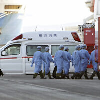 Members of Japan Self Defense Forces walk into the quarantined cruise ship Diamond Princess in the Yokohama Port, Feb. 9, 2020, in Yokohama, Japan (AP Photo/Eugene Hoshiko)
