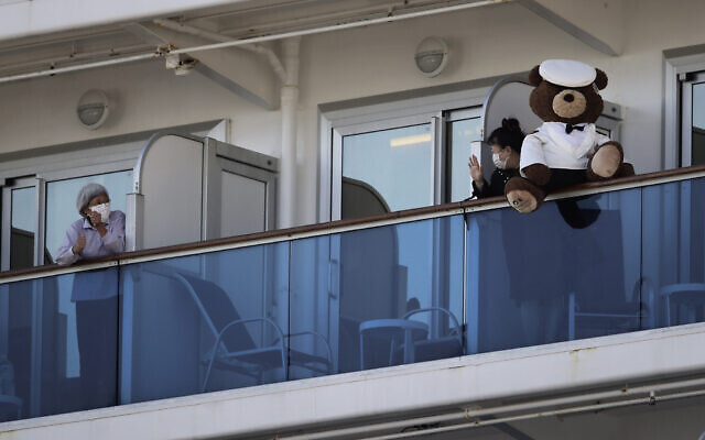 A woman with a teddy bear waves to another passenger quarantined on the Diamond Princess cruise ship in Yokohama, near Tokyo,, February 11, 2020. (AP/Jae C. Hong)