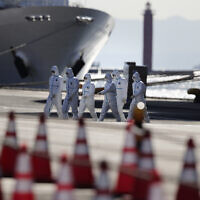 Medical workers with protective suites walk away from the quarantined Diamond Princess cruise ship in Yokohama, near Tokyo, Tuesday, Feb. 11, 2020. (AP/Jae C. Hong)