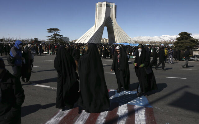Demonstrators walk on a painting of the US flag in front of the Azadi (Freedom) tower during an annual rally celebrating 41st anniversary of Islamic Revolution, in Tehran, Iran, Feb. 11, 2020  (AP Photo/Vahid Salemi)