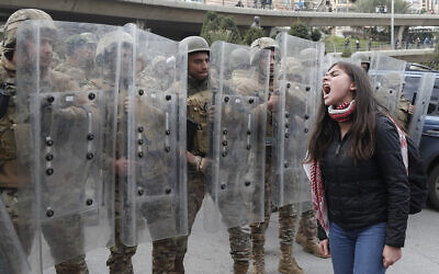 A protester shouts slogans in front of army soldiers during a protest against a parliament session vote of confidence for the new government in downtown Beirut, Lebanon, Feb. 11, 2020  (AP Photo/Hussein Malla)