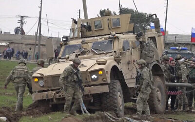 In this frame grab from video, people and soldiers gathering next to an American military convoy stuck in the village of Khirbet Ammu, east of Qamishli city, Syria, on February 12, 2020. (AP Photo)
