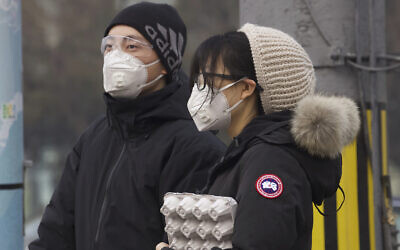 Residents wearing masks wait at a traffic light in Beijing, China, on February 13, 2020. (AP Photo/Ng Han Guan)