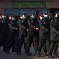 Policemen wear face masks as they march in formation outside the Beijing Railway Station in Beijing, Feb. 15, 2020 (AP Photo/Mark Schiefelbein)
