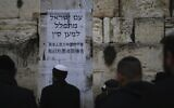 Jews pray at the Western Wall, in Jerusalem's Old City, February 16, 2020. Jewish faithful held a prayer session in search of divine intervention to help stave off the coronavirus in China. Poster in Hebrew and Chinese says, 'The People of Israel  pray for China.' (Ariel Schalit/AP)