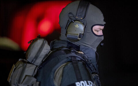 A special forces officer guards the road in front of a house that is searched through by police in Hanau, Germany Thursday, Feb. 20, 2020. Eight people were killed in shootings in and outside two hookah lounges in a southwestern German city late Wednesday, and authorities were searching for the perpetrators. (AP Photo/Michael Probst)