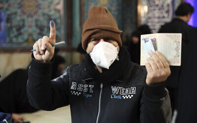 A voter shows his identification and inked finger while voting for the parliamentary elections at a polling station in Tehran, Iran, February 21, 2020. (AP Photo/Ebrahim Noroozi)
