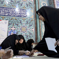 A voter registers to cast her vote during the parliament elections at a polling station in Tehran, Iran, February 21, 2020. (AP Photo/Ebrahim Noroozi)