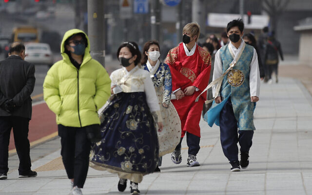 Visitors wearing face masks walk near the Gwanghwamun, the main gate of the 14th-century Gyeongbok Palace, and one of South Korea's well-known landmarks, in Seoul, South Korea, February 22, 2020.  (Lee Jin-man/AP)
