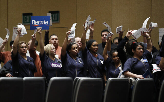 Casino workers hold up presidential preference cards as they support Democratic presidential candidate Sen. Bernie Sanders, I-Vt., during a presidential caucus at the Bellagio hotel-casino, Saturday, Feb. 22, 2020, in Las Vegas. (AP/John Locher)