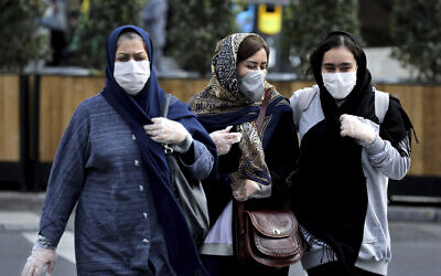 People wear masks to help guard against the Coronavirus on a street in downtown Tehran, Iran, Sunday, Feb. 23, 2020. (AP/Ebrahim Noroozi)