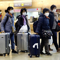 Tourists from Korea wearing protective masks walking with their belongings while waiting for a flight back to South Korea at the Ben Gurion airport near Tel Aviv, Israel, February 24, 2020. (AP Photo/Ariel Schalit)