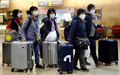 Tourists from Korea wearing protective masks walking with their belongings while waiting for a flight back to South Korea at Ben Gurion airport near Tel Aviv, February 24, 2020. (AP Photo/Ariel Schalit)