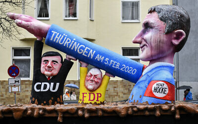 A carnival float depicts far-right AfD politician Bjoern Hoecke, whose arm is raised by CDU politician Mike Mohring and FDP politician Thomas Kemmerich at the Thuringa elections, seen prior the traditional carnival parade in Duesseldorf, Germany, on Feb. 24, 2020.  (AP Photo/Martin Meissner)