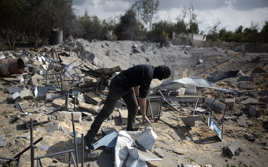 A masked Palestinian checks the damage following overnight Israeli airstrikes on an Islamic Jihad military base in the town of Khan Younis, Southern Gaza Strip, Monday, Feb. 24, 2020. (AP/Khalil Hamra)