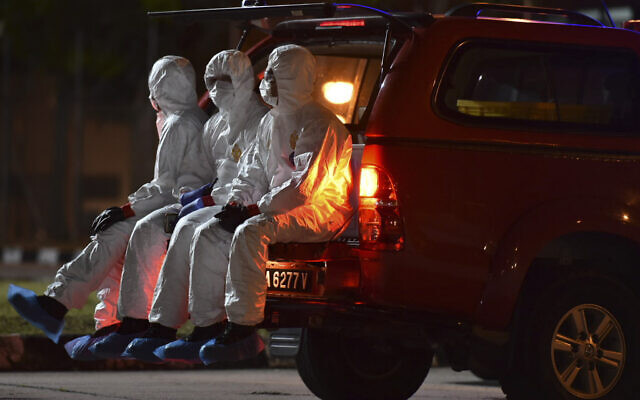 Health workers wearing full protective suits wait for the arrival of evacuated Malaysians from China's Wuhan, the epicenter of the coronavirus outbreak, at Kuala Lumpur International Airport in Sepang, Malaysia, on February 26, 2020. (Muzzafar Kasim/Malaysia's Ministry of Health via AP)