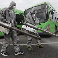 Workers wearing protective suits spray disinfectant as a precaution against the coronavirus at a bus garage in Seoul, South Korea,, February 26, 2020. (AP Photo/Ahn Young-joon)
