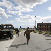 Italian Army soldiers check transit to and from the cordoned areas in Turano Lodigiano, Italy, Feb. 26, 2020  (AP Photo/Antonio Calanni)