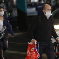 Passengers wearing masks as a precaution against the spread of the new coronavirus COVID-19 arrive to the Sao Paulo International Airport in Sao Paulo, Brazil, Wednesday, Feb. 26, 2020. (AP/Andre Penner)