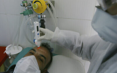 A man gets tested for COVID-19 in Algiers, Algeria, Wednesday, Feb. 26, 2020. (AP/Anis Belghoul)