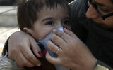 A woman helps his boy to put on a mask in downtown Tehran, Iran, February 27, 2020. (AP Photo/Vahid Salemi)