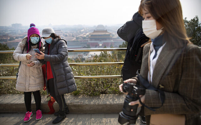 Visitors wearing face masks take photos at a park overlooking the Forbidden City in Beijing, Feb. 28, 2020 (AP Photo/Mark Schiefelbein)