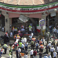 Police and medics surround the scene of a suicide bombing inside Jerusalem's Sbarro restaurant, Thursday, August 9, 2001. Fifteen people were killed, and 130 injured. (AP Photo/Peter Dejong)