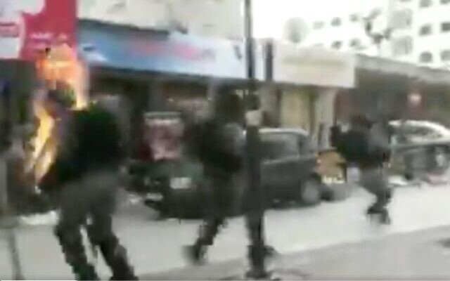 Screen capture from video of a border police engulfed in flames after he was hit by a Molotov cocktail thrown by a Palestinian rioter in the West Bank city of Hebron, February 3, 2020. (Twitter)