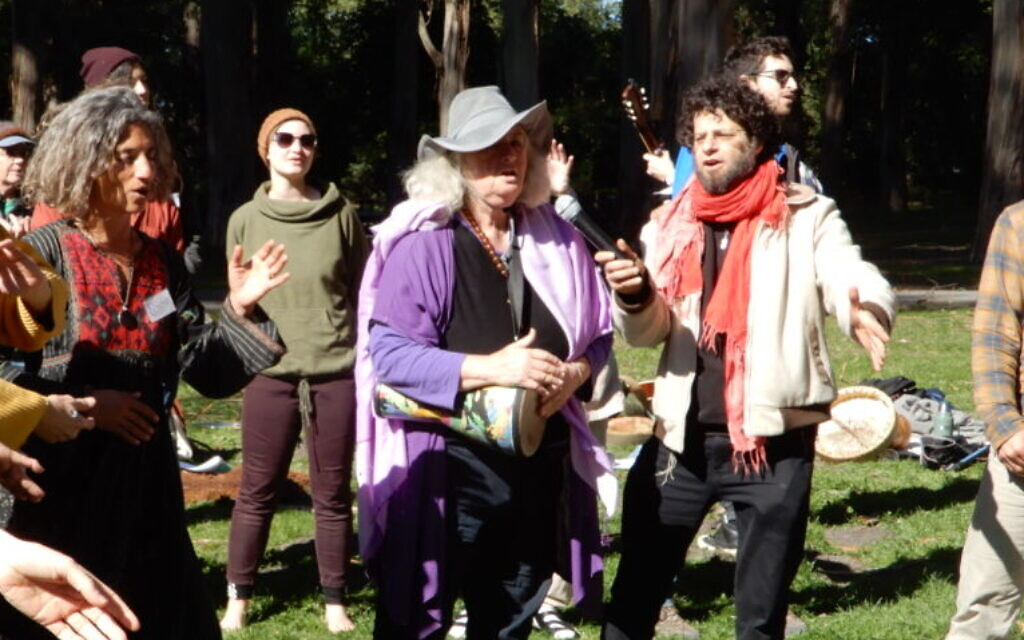 Starhawk, in purple, plays the drum during an opening song at a Wilderness Torah/JeWitch Collective Tu B'Shvat event outside of San Francisco on February 9, 2020. (Melanie Lidman/Times of Israel)