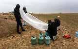Illustrative: Palestinian men prepare a flammable object to be flown toward Israel, near the Israel-Gaza border east of Rafah in the southern Gaza Strip, on January 18, 2020. (Abed Rahim Khatib/ Flash90)