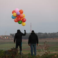 Palestinian men prepare an incendiary device to be flown toward Israel, near the Israel-Gaza border east of Al-Bureij refugee camp in the central Gaza Strip, January 22, 2020. (Ali Ahmed/Flash90)