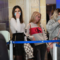 People wear face masks at Ben Gurion International Airport following reports about the deadly coronavirus having spread worldwide, February 2, 2020. (Avshalom Shoshani/Flash90)