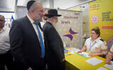Interior Minister Aryeh Deri, left, and Health Minister Yaakov Litzman visit medical personnel at Ben Gurion International Airport following reports about the deadly coronavirus, February 02, 2020. (Avshalom Shoshani/Flash90)