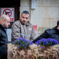 Sanad Al-Turman, suspect in the car ramming attack near the First Station center in Jerusalem on February 6, 2020, is accompanied by prison guards outside the Jerusalem Magistrates Court on February 7, 2020 (Yonatan Sindel/Flash90)