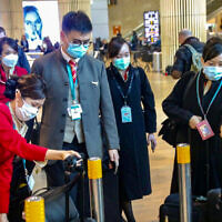 People wear face masks at the Ben Gurion International Airport, following reports about the deadly coronavirus, which originated in China, and has worldwide reach. February 17, 2020. (Avshalom Shoshani/Flash90)