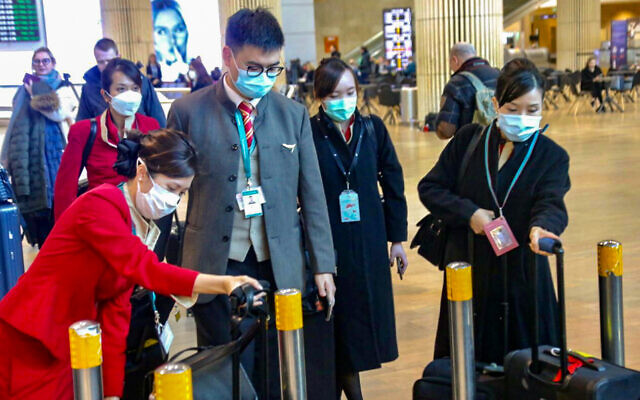 People wear face masks at Ben Gurion Airport following reports about the deadly coronavirus, February 17, 2020. (Avshalom Shoshani/Flash90)