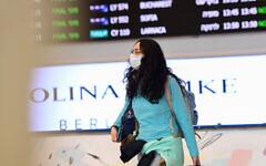 People wear face masks at Ben Gurion International Airport following reports about the deadly coronavirus having spread worldwide, February 17, 2020. (Avshalom Shoshani/Flash90)