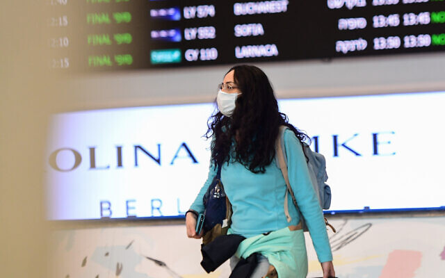People wear face masks at the Ben Gurion International Airport following reports about the deadly coronavirus, originated in China, having spread worldwide. February 17, 2020. (Avshalom Shoshani/Flash90)