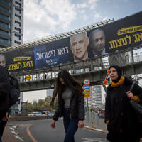 Blue and White election campaign poster showing party leader Benny Gantz and Prime Minister Benjamin Netanyahu with a Hebrew slogan reading 'Netanyahu cares only for himself,' February 18, 2020. (Miriam Alster/FLASH90)