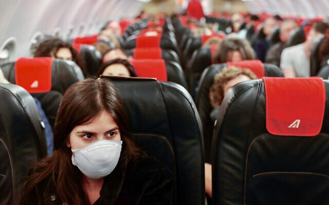 Illustrative: A woman wears a face mask on a flight from Ben Gurion International Airport to Rome's Fiumicino airport on February 21, 2020. (Nati Shohat/Flash90)