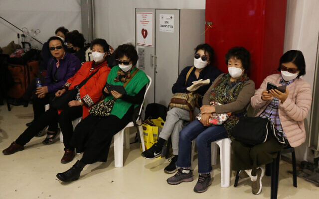 South Korean tourists being forced out of the country wear masks as they wait for a flight in an isolation area at Ben Gurion International airport on February 24, 2020. (Flash90)