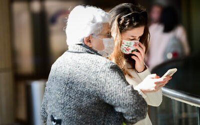 People wearing face masks against the coronavirus at Ben Gurion Airport on February 27, 2020. (Avshalom Shoshani/Flash90)