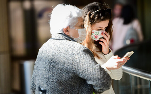 People wearing face masks against the coronavirus at Ben Gurion International Airport on February 27, 2020. (Avshalom Shoshani/Flash90)