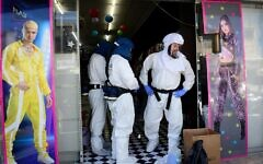 Workers disinfect a toy shop in Or Yehuda, after a man who works at the shop and returned from Italy tested positive for coronavirus February 28, 2020 (Flash90)