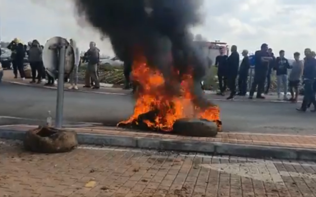 Har Gilo residents burn tires at the entrance to the West Bank settlement to protest the government's reported plans to quarantine some 200 South Korean tourists there, February 23, 2020. (Screen capture: Twitter)