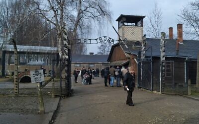 Visitors walk through the infamous gate reading 'Arbeit Macht Frei,' or 'work will make you free,' at the former site of Auschwitz-Birkenau, January 28, 2020. (Yaakov Schwartz/Times of Israel)